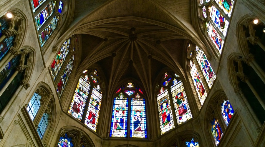 Admire gothic vault and medieval stained glass windows